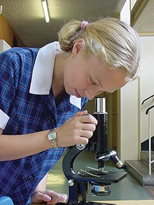 Girl looking from microscope in science laboratory