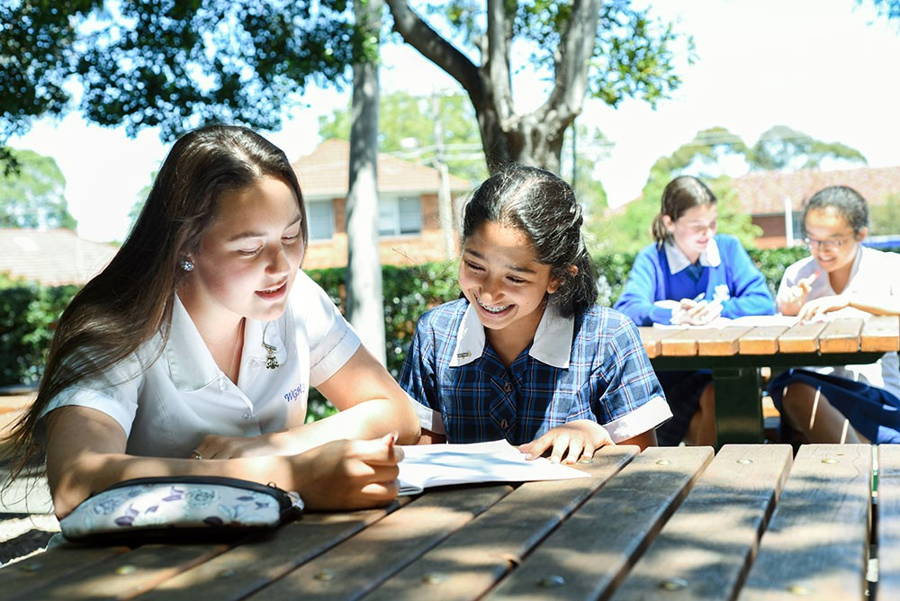 Girls learning and discussing at Willoughby Girls High School's playground desk